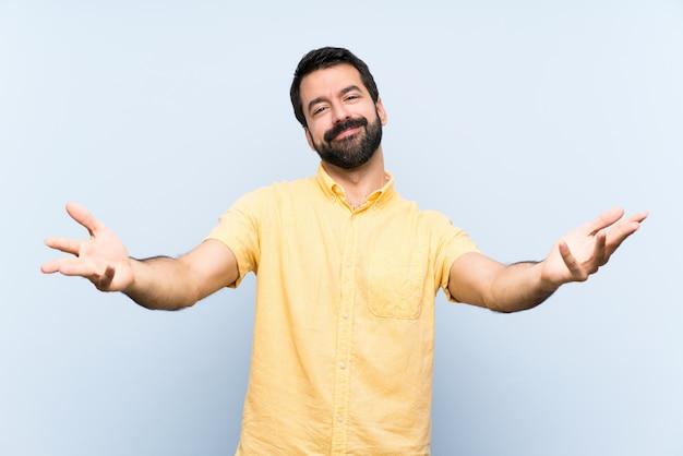 Giovane con la barba sopra la parete blu isolata che presenta e che invita a venire con la mano