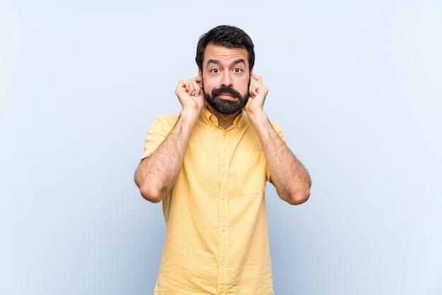 Giovane con la barba sopra la parete blu isolata frustrata e che copre le orecchie