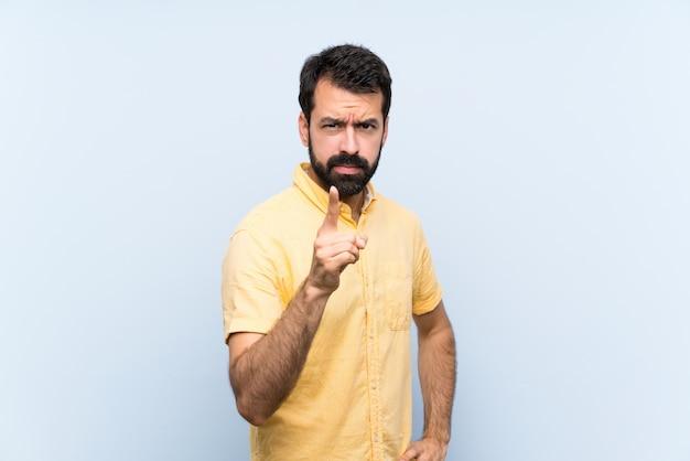 Giovane con la barba sopra la parete blu isolata frustrata e che indica la parte anteriore