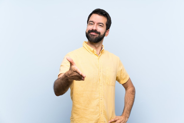 Giovane con la barba sopra le mani stringere blu isolate per la chiusura molto