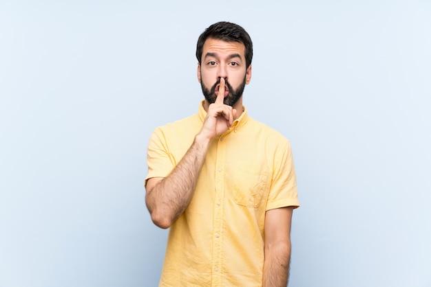 Giovane con la barba sul blu che mostra un segno di gesto di silenzio che mette il dito in bocca