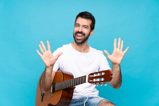 Giovane con la chitarra sopra il blu isolato che conta dieci con le dita