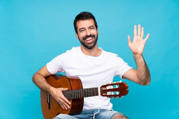 Giovane con la chitarra sopra il saluto blu isolato con la mano con l'espressione felice