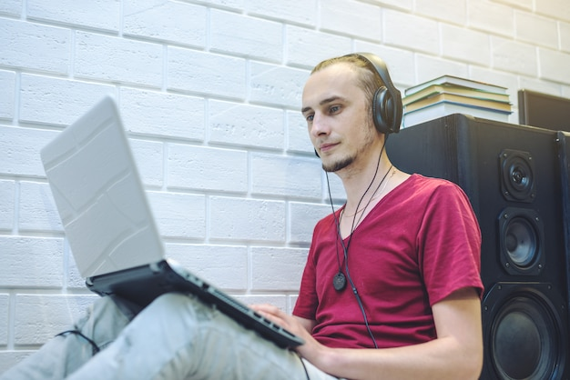 Giovane con le cuffie che ascolta le lezioni e che lavora ad un computer portatile. il concetto di tecnologia e educazione moderna