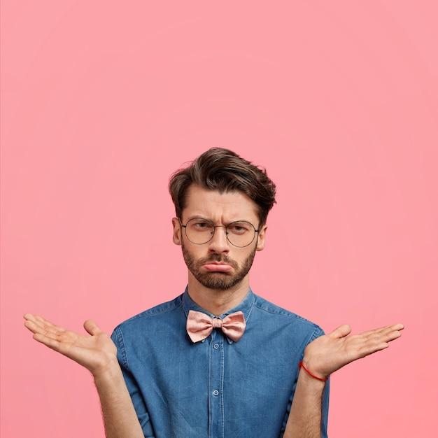 Giovane con occhiali rotondi e papillon rosa