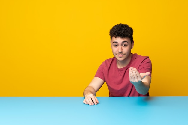 Giovane con parete colorata e tavolo che invita a venire con la mano. felice che tu sia venuto