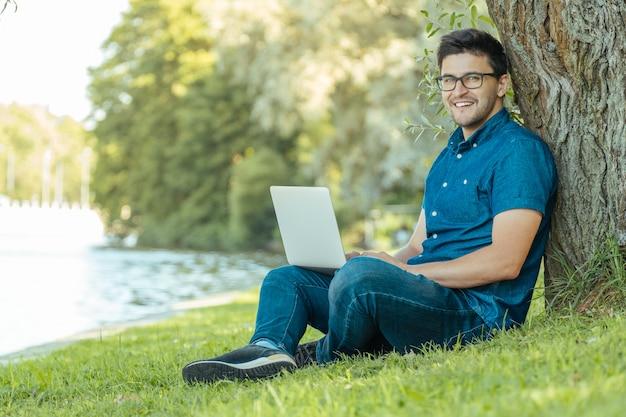 Giovane con seduta all'aperto del computer portatile sull'erba