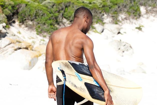 Giovane con tavola da surf in spiaggia