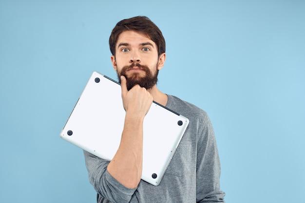 Giovane con un computer portatile in mano su una parete blu-chiaro che propone emozionalmente