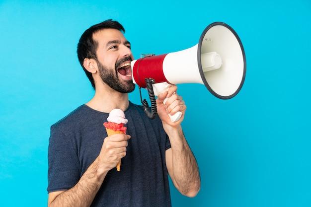 Giovane con un gelato della cornetta sopra la parete blu isolata che grida tramite un megafono