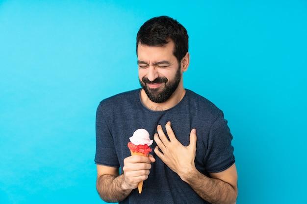 Giovane con un gelato di cornetta che ha un dolore al cuore