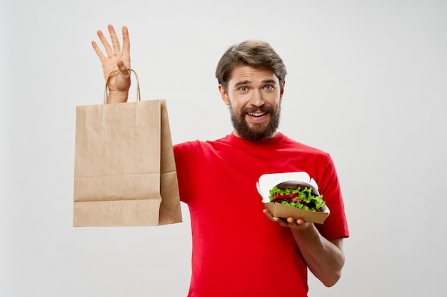 Giovane con un succoso hamburger nelle sue mani, un uomo che mangia un hamburger