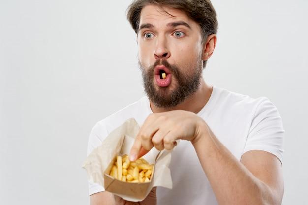 Giovane con un succoso hamburger nelle sue mani, un uomo mangia patatine