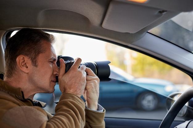 Giovane con una macchina fotografica del dslr in un'automobile