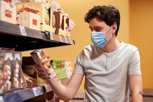 Giovane con una maschera che esamina gli spuntini in un supermercato