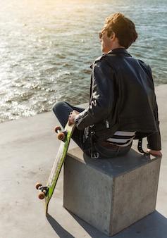 Giovane con uno skateboard vicino al mare