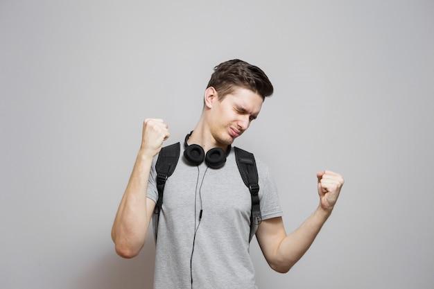 Giovane con uno zaino in cuffia su uno sfondo grigio. lo studente con una borsa ascolta la musica.