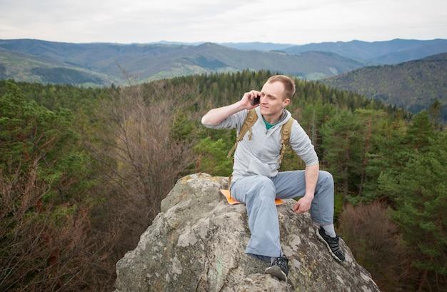 Giovane con uno zaino seduto sulla cima della roccia, guardando lontano e parlando al telefono