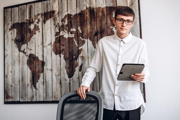 Giovane, concentrato uomo d'affari in bicchieri detiene un tablet. concetto di lavoro d'ufficio