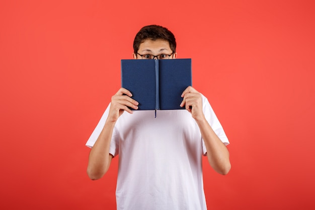 ? giovane concepito in vetri che coprono il fronte di libro su fondo rosso