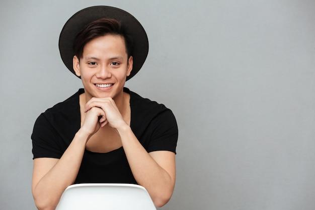 Giovane condizione asiatica felice dell'uomo isolata sopra la parete grigia