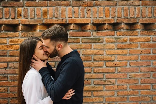 Giovane coppia a baciarsi davanti al muro