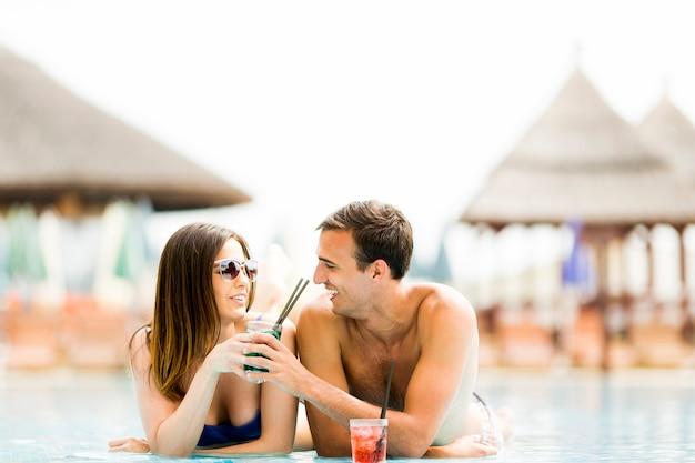 Giovane coppia a bordo piscina