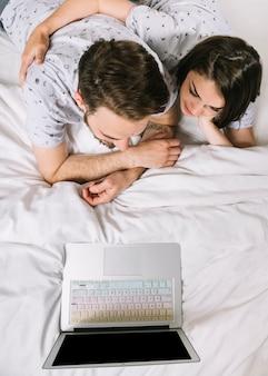 Giovane coppia a letto usando il portatile