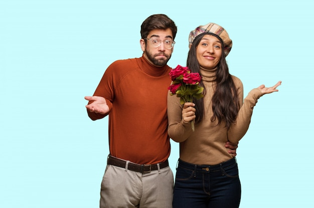 Giovane coppia a san valentino dubitando e alzando le spalle