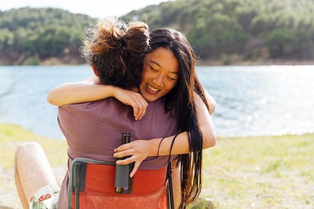 Giovane coppia abbracciando sulla riva del fiume