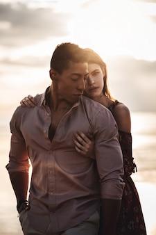 Giovane coppia abbracciarsi in un tramonto