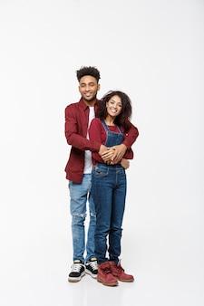 Giovane coppia afro-americana che abbraccia, con un sorriso.
