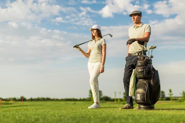 Giovane coppia al carrello da golf