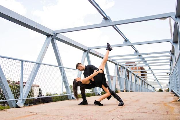 Giovane coppia attraente tangoing sul ponte