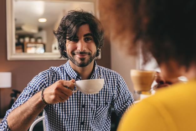 Giovane coppia bere un caffè al caffè, rilassato e confortevole, guardando a vicenda.
