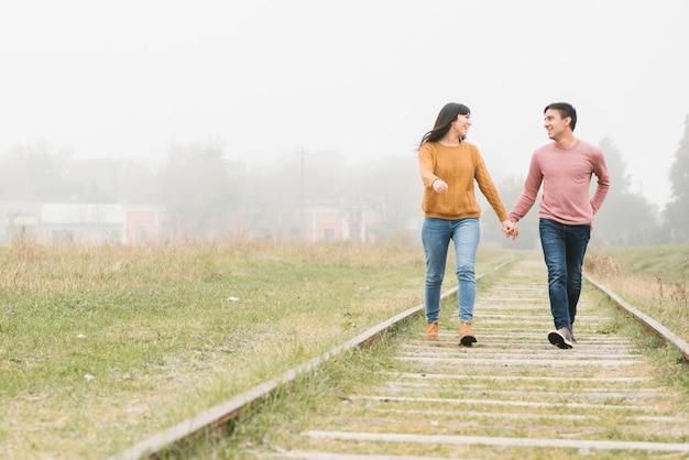 Giovane coppia camminando lungo le piste