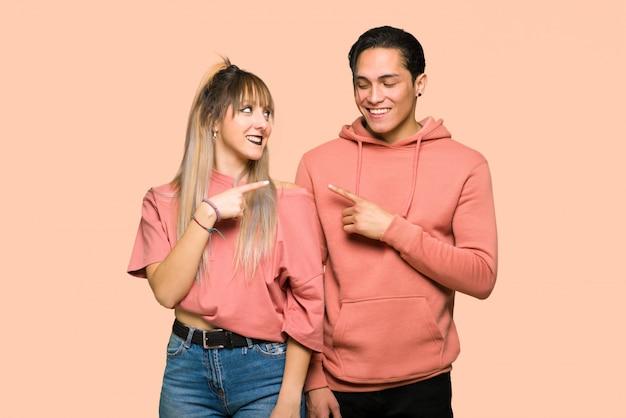 Giovane coppia che punta a lato per presentare un prodotto su sfondo rosa