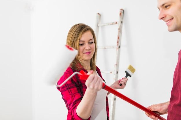 Giovane coppia che si prepara a dipingere le pareti