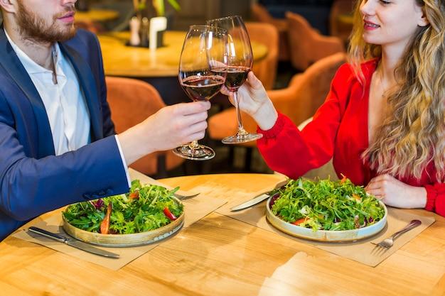 Giovane coppia con clanging bicchieri al tavolo