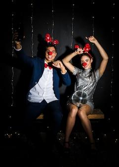 Giovane coppia con fasce di corna di cervo e nasi divertenti con palla da discoteca
