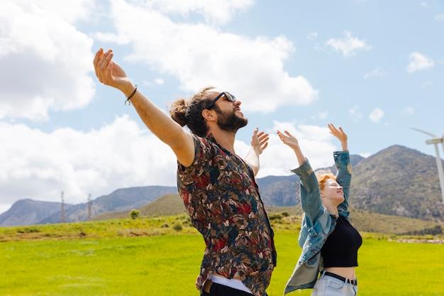 Giovane coppia con le mani in alto in natura
