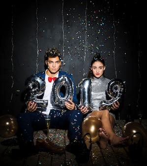 Giovane coppia con numeri di palloncini argento tra lancio di coriandoli