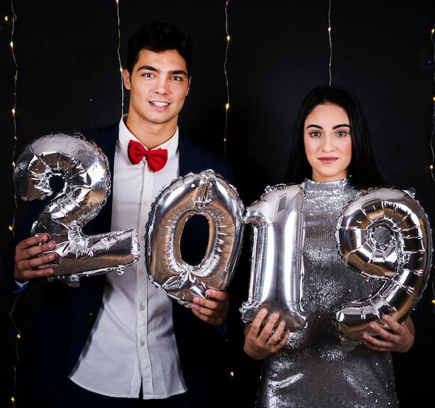 Giovane coppia con numeri di palloncini