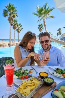 Giovane coppia con smartphone nel ristorante della piscina