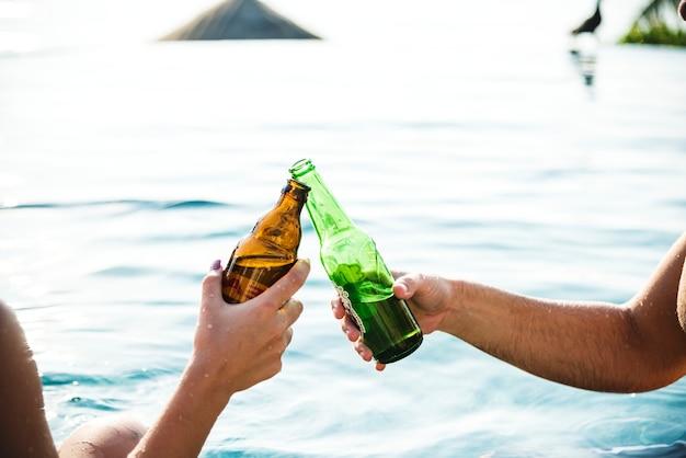 Giovane coppia con una birra in piscina