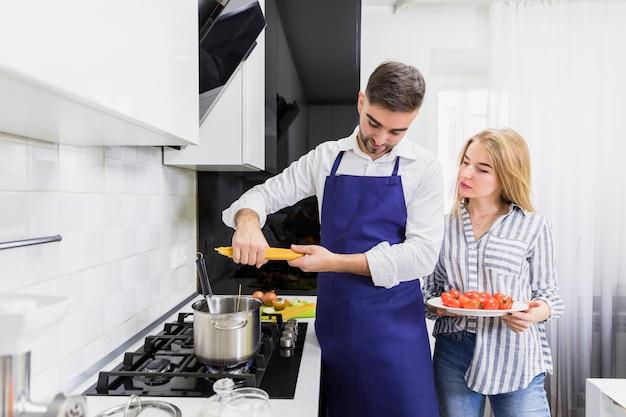 Giovane coppia di mettere gli spaghetti in pentola con acqua bollita