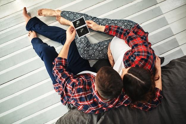 Giovane coppia di sposi in attesa di un bambino. belle coppie che giacciono in camera da letto fanno piani per la nascita di un bambino. primo figlio, dopo il parto, giovane famiglia.