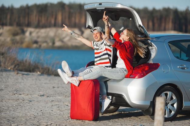 Giovane coppia di sposi in vacanza. viaggio in macchina. viaggio in auto. giovani emozionali che viaggiano.