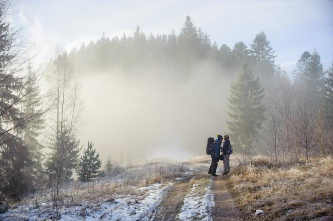 Giovane coppia di turisti che soggiornano nei boschi invernali sulla strada e bacio
