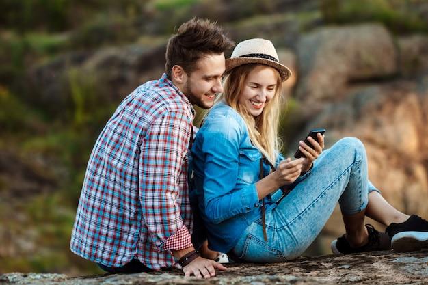 Giovane coppia di viaggiatori sorridenti, guardando il telefono